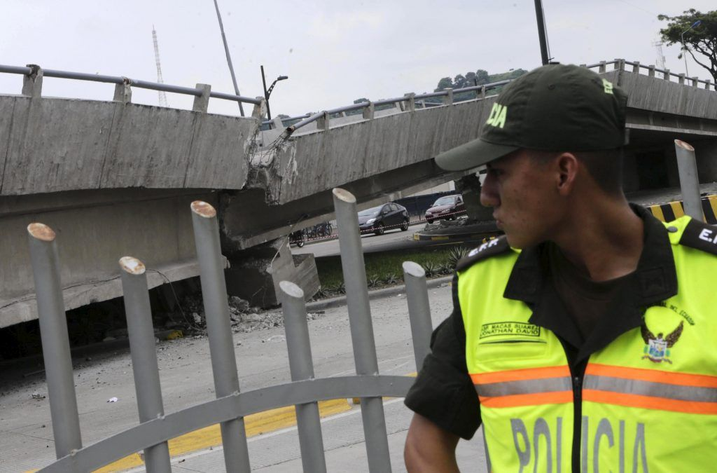 A police officer stands guard next to a collapsed bridge after an earthquake struck off the Pacific coast, in Guayaquil, Ecuador, April 17, 2016. REUTERS/Henry Romero