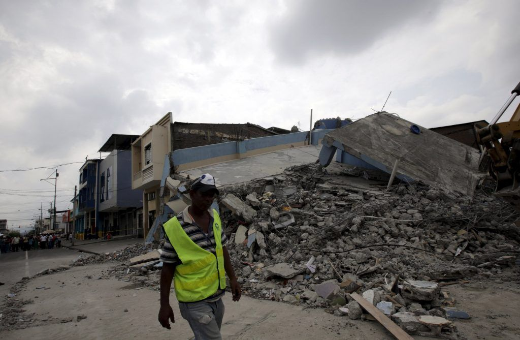 A worker walks past a collapsed building after an earthquake struck off the Pacific coast, in Guayaquil, Ecuador, April 17, 2016. REUTERS/Henry Romero