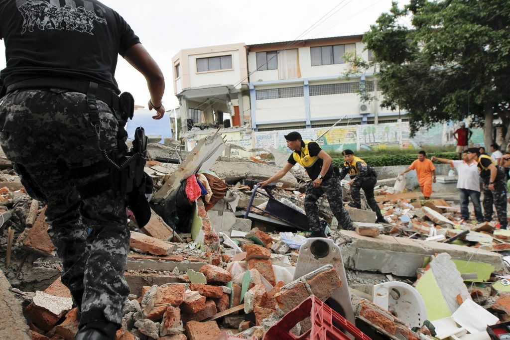 Red Cross members, military and police officers work at a collapsed area after an earthquake struck off Ecuador's Pacific coast, at Tarqui neighborhood in Manta April 17, 2016. REUTERS/Guillermo Granja TPX IMAGES OF THE DAY