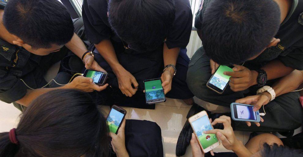 Varios jóvenes juegan al videojuego 'Pokemon Go' desde su teléfono móvil